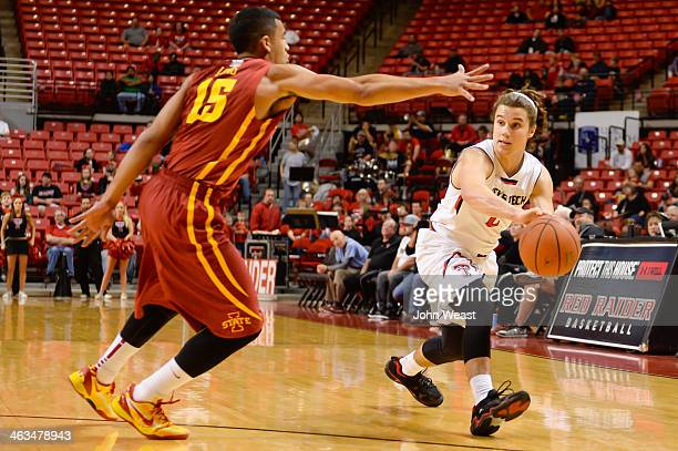 Dusty Hannahs of the Texas Tech Red Raiders passes the ball around Naz Long of the Iowa State Cyclones during game action on January 4 2014 at United...