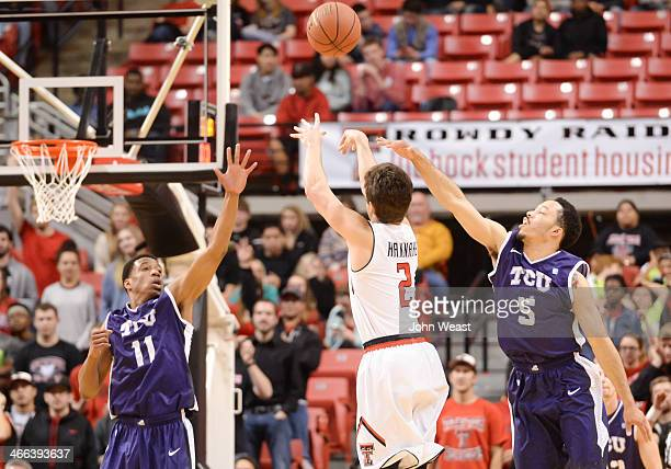 Dusty Hannahs of the Texas Tech Red Raiders shoots the ball between Brandon Parrish of the TCU Horned Frogs and Kyan Anderson of the TCU Horned Frogs...