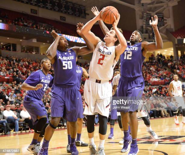 Dusty Hannahs of the Texas Tech Red Raiders shoots the ball over DJ Johnson of the Kansas State Wildcats and Omari Lawrence of the Kansas State...