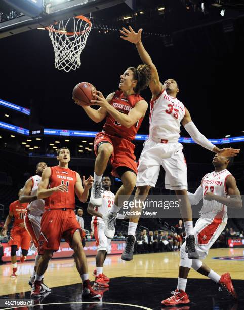 Dusty Hannahs of the Texas Tech Red Raiders takes a shot with pressure from TaShawn Thomas of the Houston Cougars during the first half at Barclays...
