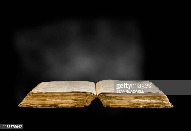 dusty old open book - religious text stock pictures, royalty-free photos & images