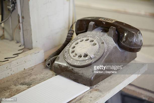 Dusty old telephone on shelf in cabinet makers workshop