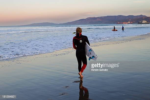 Dusty Payne of Hawaii makes his way into the lineup with a rose in his mouth in honor of the late Andy Irons on November 2, 2011 in San Francisco,...