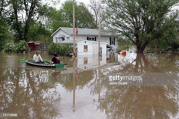 Dusty Rhoades and Fernando Julio return in a rowboat from inspecting Julio's damaged house after heavy rains caused the Missouri River to flood May 9...
