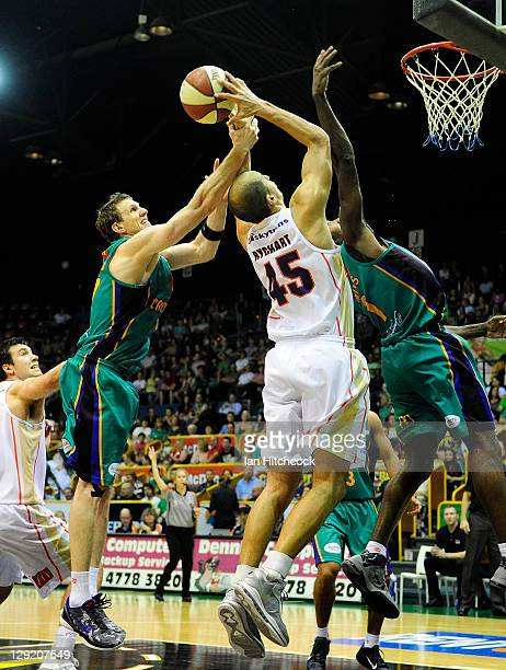 Dusty Rychart of the Taipnas contests the ball with Peter Crawford and Elvin Mims of the Crocodiles during the round two NBL match between the...