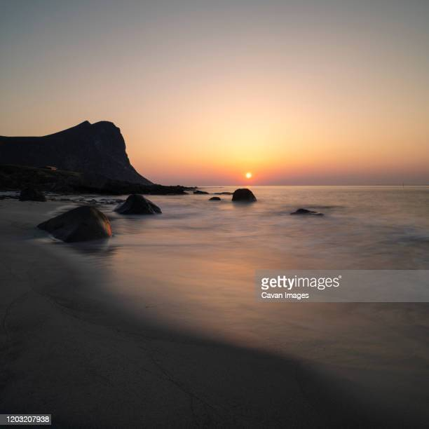dusty sunset at sand from sarah desert blew over northern norway in april 2019, myrland, flakstady, lofoten islands, norway - sarah sands stock pictures, royalty-free photos & images