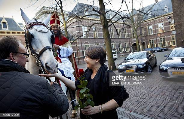 Dutch actor Patrick Mathurin dressed as black Sinterklaas gives a rose to inister of Foreign Affairs Bert Koenders at the Binnenhof, The Hague on...