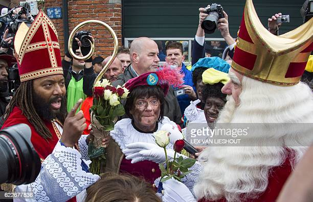 Dutch actor Patrick Mathurin dressed as Sinterklaas speaks to man also dressed in the same costume next to two women dressed as Zwarte Piet on...