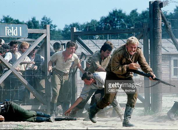 Dutch actor Rutger Hauer brandishing a rifle leads others past a concentration camp fence in the madefortelevision movie 'Escape from Sobibor' 1987...
