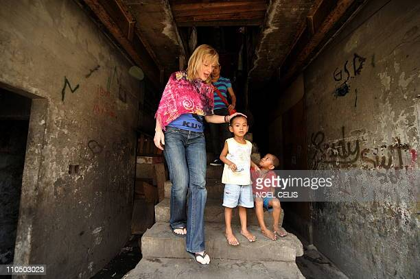 Dutch actress Johanna ter Steege touches a boy's head as she descends from a house she visited at the Aroma Compound Vitas Tondo a slum area in...