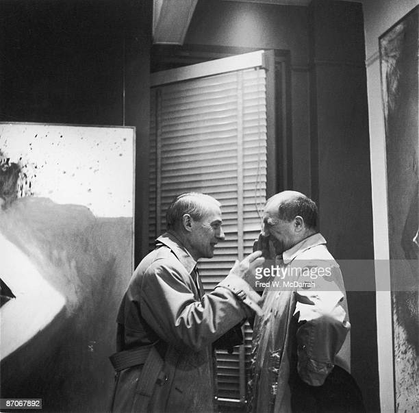 Dutch American artist Willem de Kooning and Polish American artist Jack Tworkov share a laugh at Sidney Janis Gallery New York New York March 9 1959...