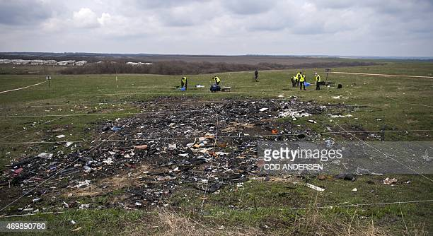 Dutch and Malaysian investigators and local authorities work on April 16 2015 at the MH17 plane crash site near the village of Grabove in the...