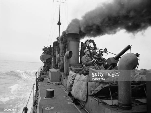 A Dutch anti aircraft gunner and spotter aim their naval gun on a target from the deck of a Royal Netherlands Navy gunboat during World War II in...