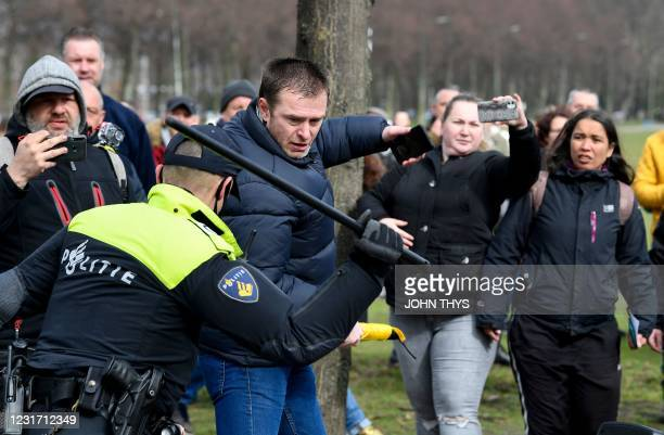Dutch anti-riot police officers react to a man during a demonstration against the government and anti-covid measures at the Malieveld in The Hague on...