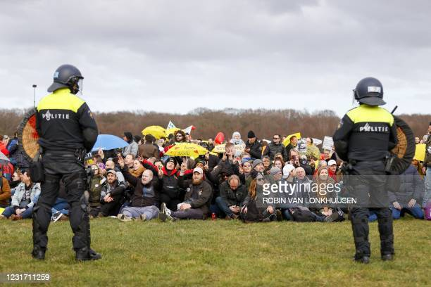 Dutch anti-riot police officers watch demostartors as they gather to protest against the government and the anti-covid measures imposed at the...