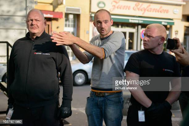 Dutch artist Dries Verhoeven stands between two security guards during a discussion of his installation 'Wanna Play' with demonstrators at...