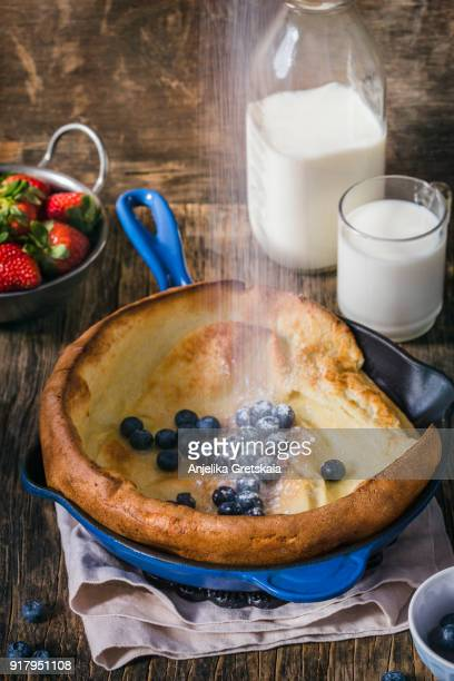 dutch baby pancakes with berries and powdered sugar baked in oven on iron pan - dutch culture stock pictures, royalty-free photos & images