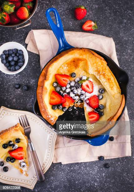 dutch baby pancakes with berries and powdered sugar baked in oven on iron pan - sugar baby imagens e fotografias de stock