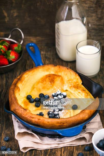 dutch baby pancakes with berries and powdered sugar baked in oven on iron pan. - sugar baby imagens e fotografias de stock