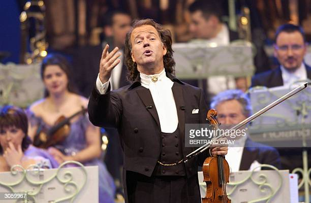 Dutch conductor and violinist Andre Rieu waves to the crowd at Bercy Palace 10 March 2004 in Paris during his French tour AFP PHOTO BERTRAND GUAY