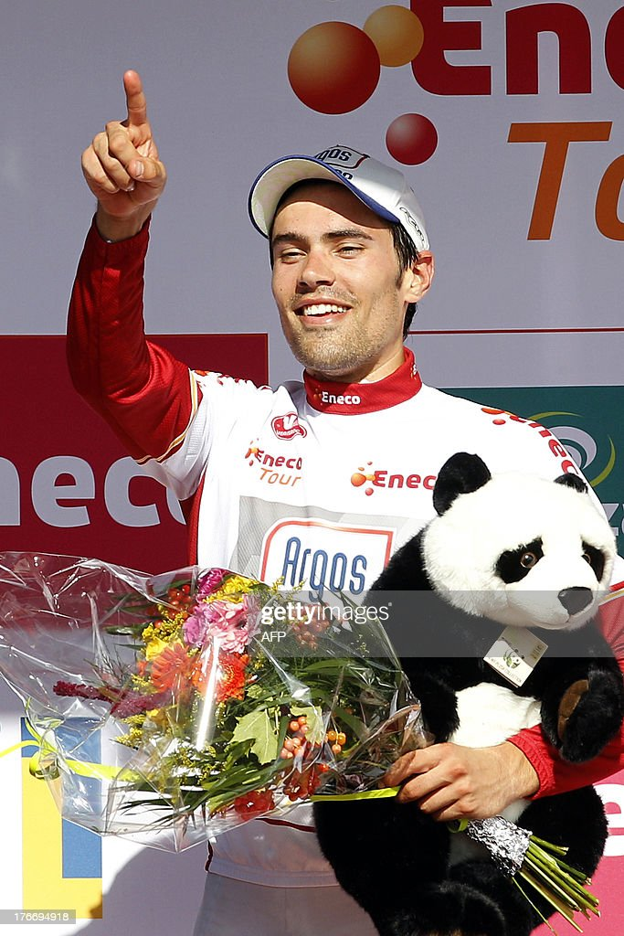Dutch cyclist Tom Dumoulin of the Argos-Shimano procycling team celebrates on the podium after winning the general classification at the sixth stage of the Eneco Tour cycling race, from Riemst to La Redoute, on August 17, 2013. Team Argos climber Dumoulin's fourth-placed finish helped him move into an eight-second lead over Czech Stybar with Ukrainian Andriy Grivko up to third at 23sec. AFP PHOTO/ANP/ BAS CZERWINSKI netherlands out