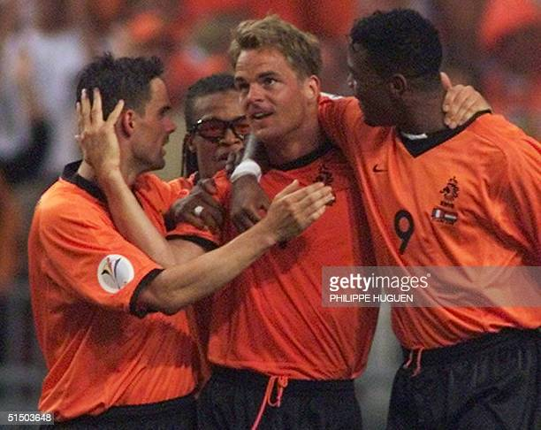 Dutch defender and captain Frank de Boer is congratulated by his teammates Marc Overmars Edgar Davids and Patrick Kluivert after scoring his team's...