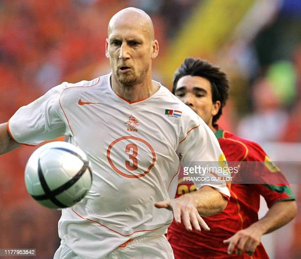 Dutch defender Jaap Stam controls the ball in front of Portuguese midfielder Deco 30 June 2004 at the Alvalade stadium in Lisbon during the Euro 2004...