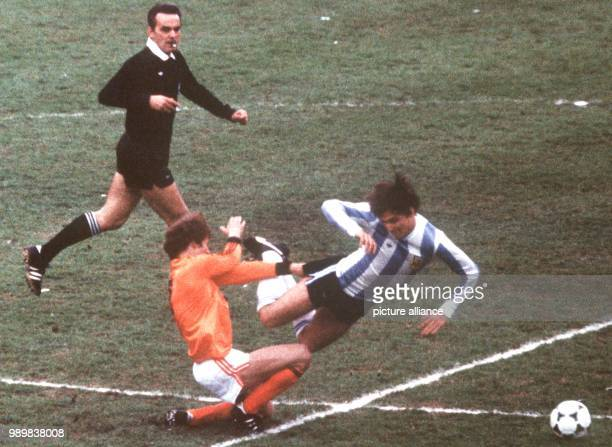 Dutch defender Jan Poortvliet brings down Argentine forward Daniel Bertoni with a foul which is seen by referee Sergio Gonella The Argentinean...