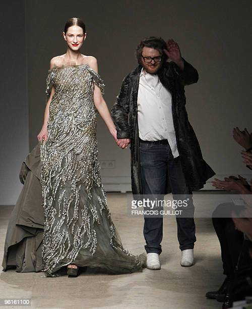 Dutch designer Josephus Thimister gestures near a model presenting one of his creation during the springsummer 2010 haute couture collection show on...