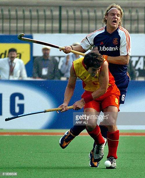 Dutch field hockey player Evers Floris and Spanish player Alex Fabregas fight for the ball during the sixnation Champions Trophy Tournament match...