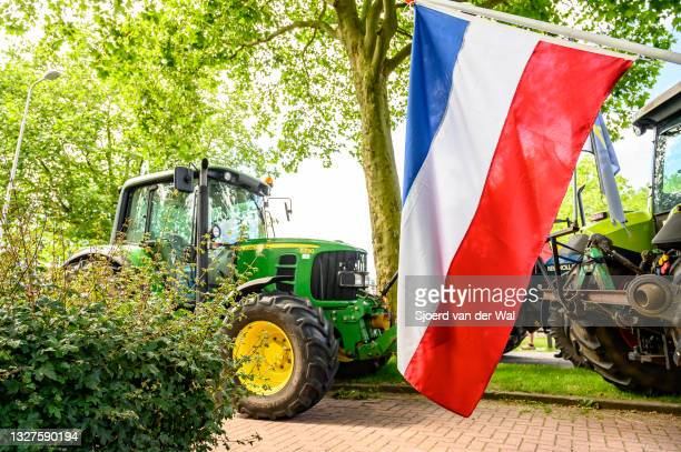 Dutch flag hanging upside down at a protest where farmers are parking their tractors on the side of the street in front of the Zwolle office of the...