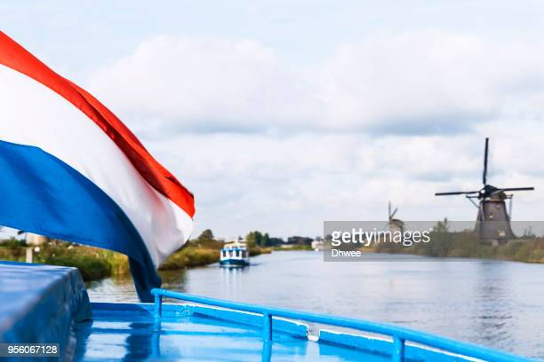 dutch flag waving in the wind against windmills, kinderdijk, netherlands - nederlandse vlag stockfoto's en -beelden