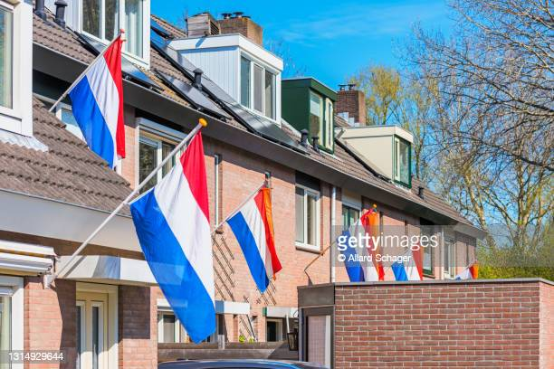 dutch flags hanging outside houses in alkmaar, netherlands to celebrate king's day on april 27, a national holiday in the netherlands and birthday of king willem-alexander - flag stock pictures, royalty-free photos & images