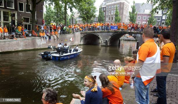 Dutch football supporters wait on a canal in Amsterdam on July 13 2010 for the Dutch football team to pass during a ceremonial boat parade on the...