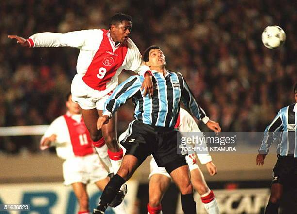 Dutch football team Ajax forward Patrick Kluivert heads the ball in the air ahead of Gremio defender Catalino Rivarola 28 November during the...