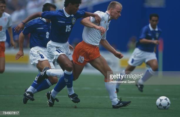 Dutch footballer Dennis Bergkamp makes a penetrating run with the ball between Brazilian players captain Dunga and Marcio Santos during play in the...