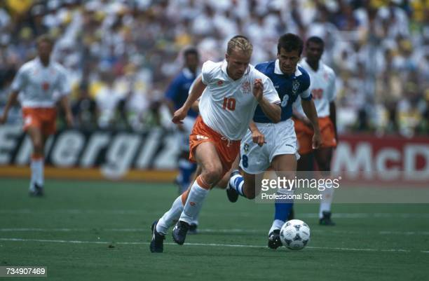 Dutch footballer Dennis Bergkamp makes a run with the ball as Brazil captain Dunga follows closely during play in the 1994 FIFA World Cup...