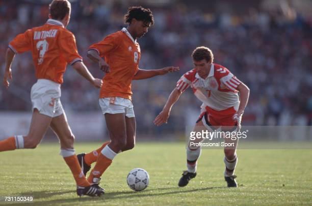 Dutch footballer Frank Rijkaard advances with the ball supported by teammate Adri van Tiggelen as Danish footballer John Jensen moves in for a tackle...