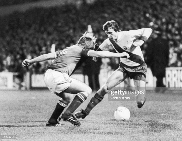 Dutch footballer Johan Cruyff running at the Ipswich defender John Stirk while playing for Barcelona.