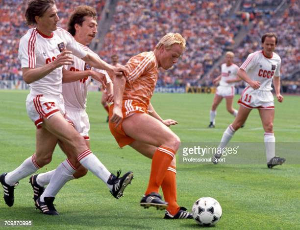 Dutch footballer Ronald Koeman of the Netherlands team is tackled for the ball by Soviet player Sergei Aleinkov during play against the Soviet Union...