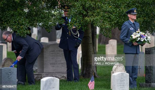 Dutch Foreign Minister Frans Timmermans and Defense Attache Air Corp Reefman duck beneath a tree as Lt Col RNLAF Perry Sommers holds flowers as the...