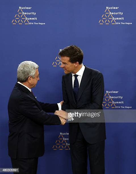 Dutch Foreign Minister Mark Rutte greets Armenian President Serzh Sarkisian upon his arrival at The World Forum in The Hague on March 24, 2014 on the...