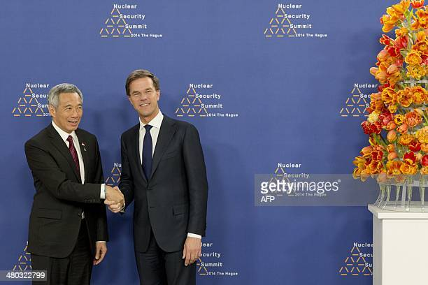 Dutch Foreign Minister Mark Rutte greets Singapore's Prime Minister Lee Hsien Loong upon his arrival at The World Forum in The Hague on March 24,...
