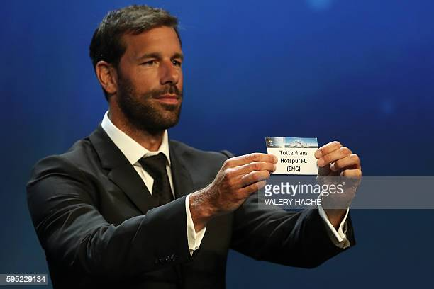 Dutch former football player Ruud van Nistelrooy shows a piece of paper bearing the name of Tottenham Hotspur FC during the UEFA Champions League...