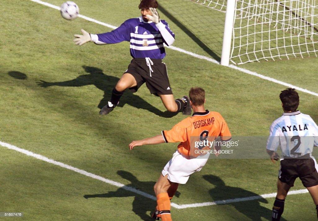 Dutch forward Dennis Bergkamp kicks the ball past : News Photo