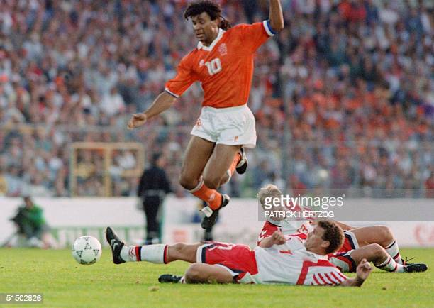Dutch forward Ruud Gullit jumps over the attempted tackle of Danish midfielder John Jensen as Henrik Larsen looks on during the European Nations...