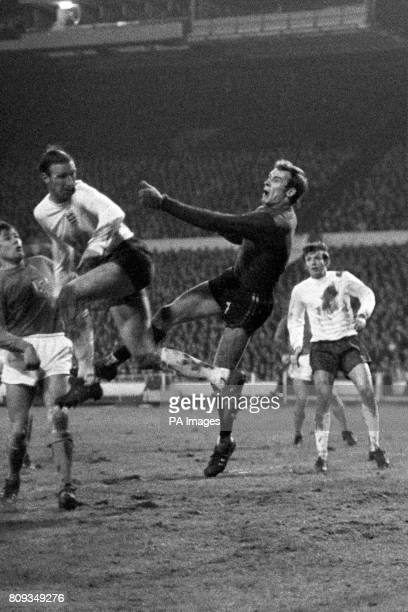 Dutch goalkeeper Jan Van Beveren jumps to clear his penalty area under pressure from England's Jackie Charlton England's Martin Peters looks on