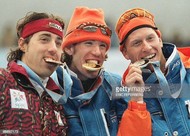 Dutch gold medalist Gianni Romme compatriot Rintje Ritsma silver and Belgium Bart Veldkamp bronze bite their medals on the podium of the men's 5000 m...