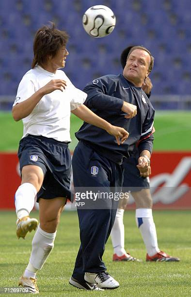 Dutch head coach of the South Korean team Dick Advocaat and South Korean defender Kim Jin Kyu fight for the ball during a training session at the...