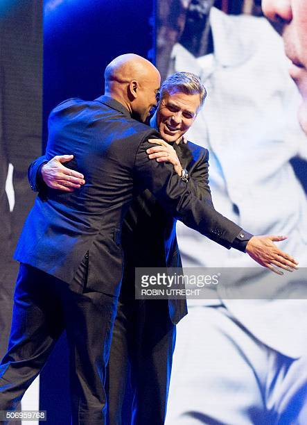 Dutch host Humberto Tan greets US actor George Clooney during the Goed Geld Gala charity event at the Carre Theatre in Amsterdam on January 26 2016...